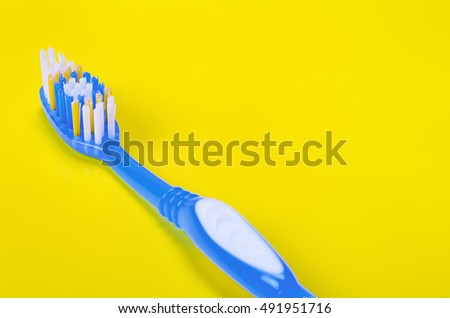 Close-up of colorful blue toothbrush on yellow background. Copyspace.