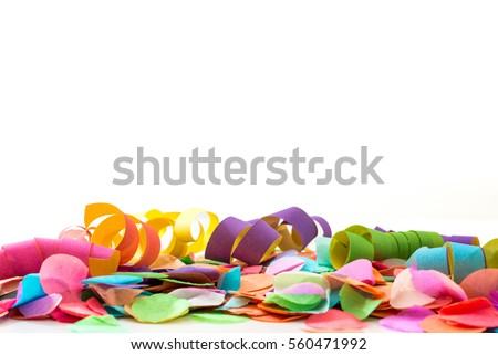 Close-up of colorful confetti and streamers in front of white background as template for birthday celebration or carnival