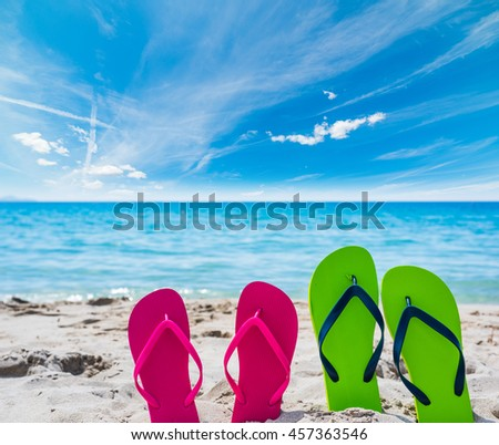 close up of colorful flip flops on the sand