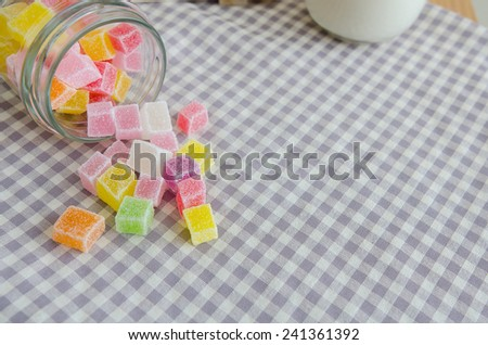 Close up of colorful fruit jelly in glass on check cloth table - stock photo