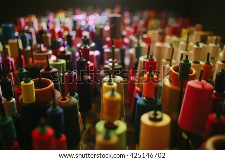 Close Up of Colorful Industrial Size Spools of Cotton Thread in Vibrant Colors of Pink, Orange, Yellow, Green and Purple viewed high angle, with a spot light - stock photo