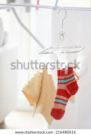 Close-up of colorful laundry pins and hanged clothes drying - stock photo