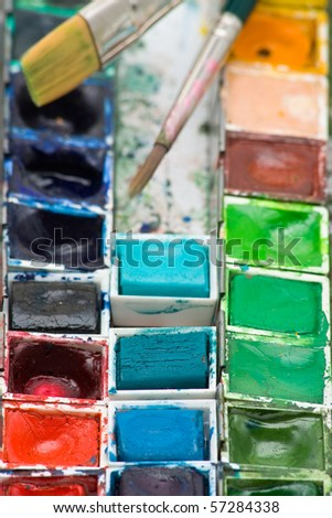 Close up of colorful paint box with water colors and brushes - stock photo