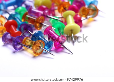 Close up of colorful pins over white background - stock photo