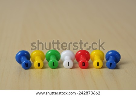 "Close Up of Colorful Push Pins with ""HOLIDAY"" on Top"
