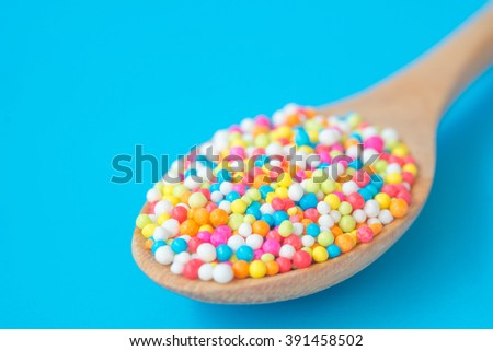 Close up of colorful rainbow sweet candies spreading pastry decoration on wooden spoon - stock photo