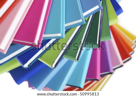 Close-up of colorful real books fan on white background, top view. - stock photo
