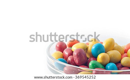 Close up of colorful round candies in a glass bowl on white background.