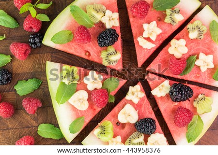 Close up of colorful watermelon pizza with fresh berries, banana, kiwi and mint on a cutting board. - stock photo