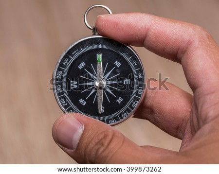 Close up of compass and point to North and hold by hand. - stock photo
