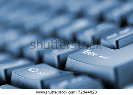 Close-up of computer keyboard. Toned in blue