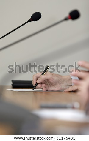 close up of conference meeting microphones and businessman writing - stock photo
