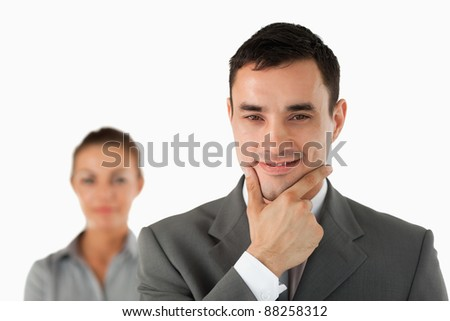 Close up of confident businessman with colleague behind him against a white background - stock photo