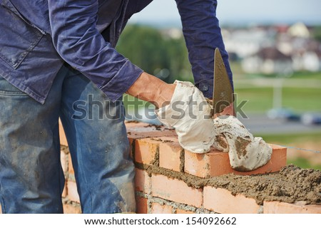 Close-up of construction process mason work with brick installation by trowel putty knife outdoors - stock photo