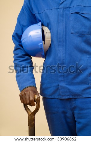 Close up of construction worker holding shovel and blue hard hat - stock photo
