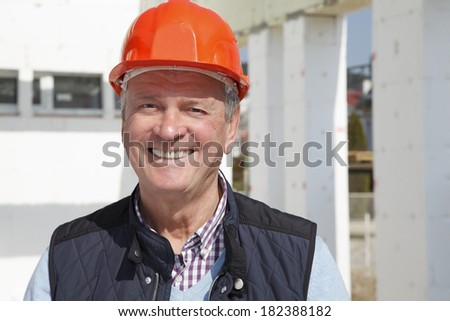 Close-up of construction worker standing in front of construction site.