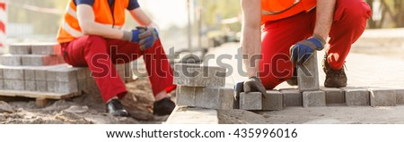 Close-up of construction workers laying the walkway - stock photo