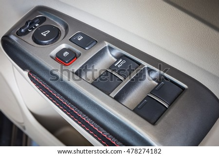 Close Up of controls button switch on the door. Interior detail in luxury modern car. select focus