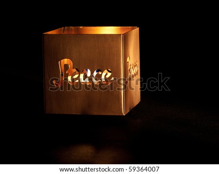 Close up of copper candle holder with the word, Peace, lit by candle. - stock photo