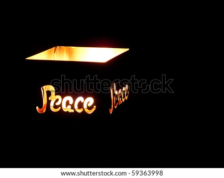 Close up of copper candle holder with word, peace, lit by candle. - stock photo