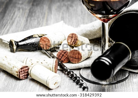 Close-up of corks, corkscrew, wine glass and bottle with a textile on a wooden background