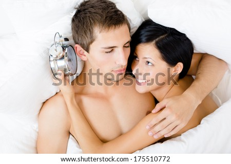 Close up of couple lying in bed-room. Woman holds alarm clock near the ear of man, top view - stock photo