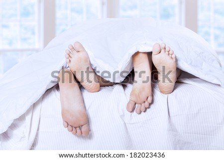 Close-up of couple's feet having intimate relation in bed - stock photo