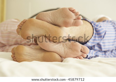 Close Up Of Couple's Feet Relaxing On Bed At Home - stock photo