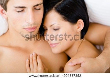 Close up of couple sleeping in bed, top view. Concept of love and affection - stock photo