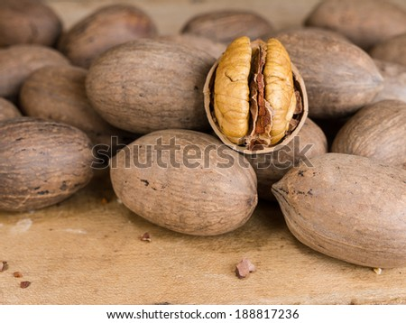 Close up of cracked and whole pecan tree nuts. - stock photo