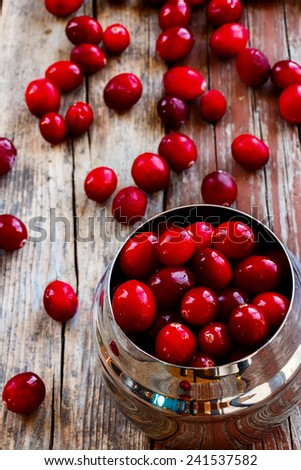 Close up of cranberries over rustic wooden background. Selective focus - stock photo