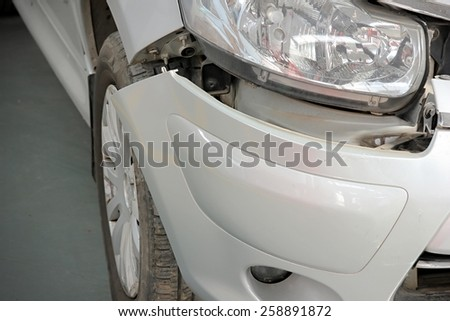 Close-up of crashed car's front area with cracks. - stock photo