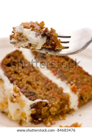 Close up of  creamy sweet walnut carrot cake on a fork with white background. - stock photo
