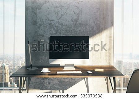 Close up of creative designer desktop with blank computer monitor, coffee cup and other items in interior with city view and sunlight. Mock up, 3D Rendering