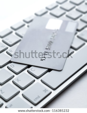 Close up of credit card on a laptop keyboard. Concept of internet buying - stock photo