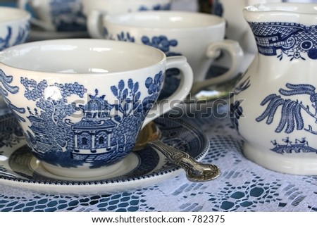 Close up of cup blue patterned china tea set on lace tablecloth - stock photo