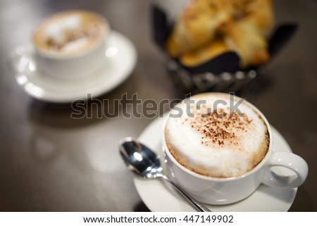 close up of cup of coffee and croissants - stock photo