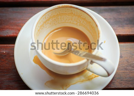 Close up of cup of coffee and splashes around on the wood table - stock photo