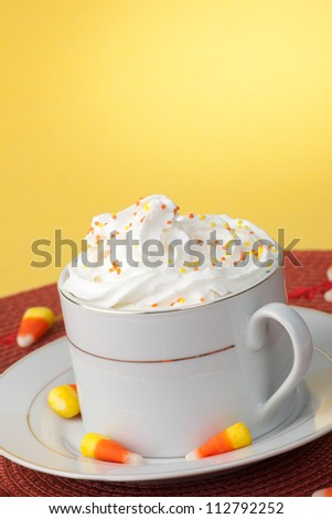 Close up of cup of fresh, delicious Pumpkin Spice Coffee, and candy corn - stock photo