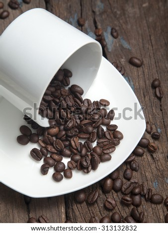 Close up of cup with coffee beans in dark light.