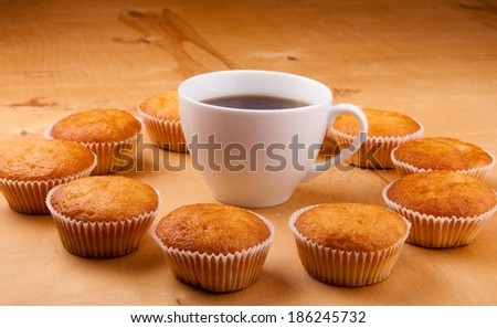 Close-up of cupcakes and cup of tea on wooden board. - stock photo