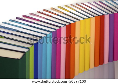 Close-up of curve aligned in rainbow colors paper wrapped books with blank spine facing front, view from top-left, PHOTOGRAPH, NOT 3D RENDER. - stock photo