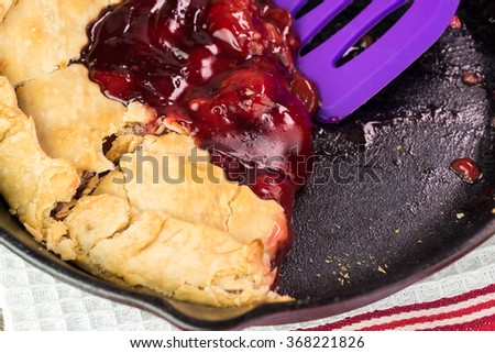 Close up of cut homemade cherry pie on iron skillet.