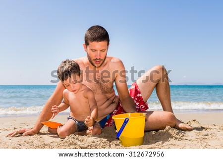 close-up of cute and smiling caucasian father and son playing with sand, pail and shovel on the beach with sea background during summer
