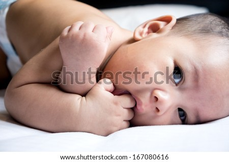 Close Up of cute Asian baby boy sucking his fingers on a white bed