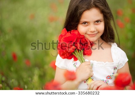 Close up of cute girl in poppy field holding flowers bouquet outdoors. Girl in poppies. Happy kid with poppies. - stock photo