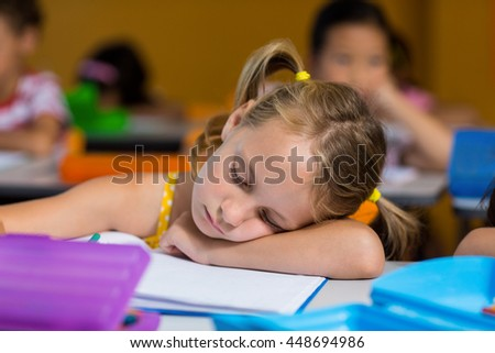 Close-up of cute girl sleeping in classroom - stock photo