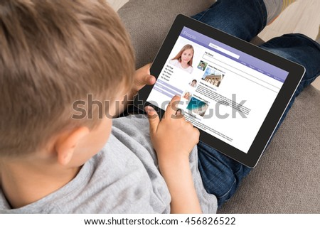Close-up Of Cute Little Boy Using Social Networking Site On Digital Tablet At Home