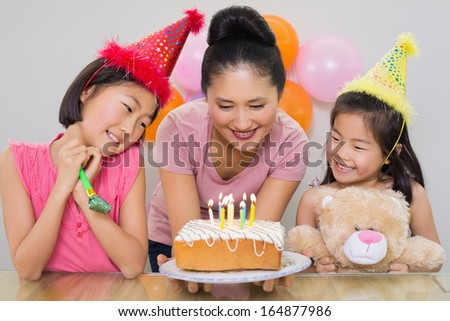 Close-up of cute little girls looking at mother with cake at a birthday party - stock photo