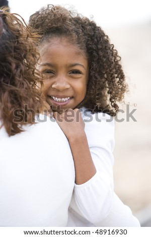 Close-up of cute six year old African-American girl in mother's arms - stock photo